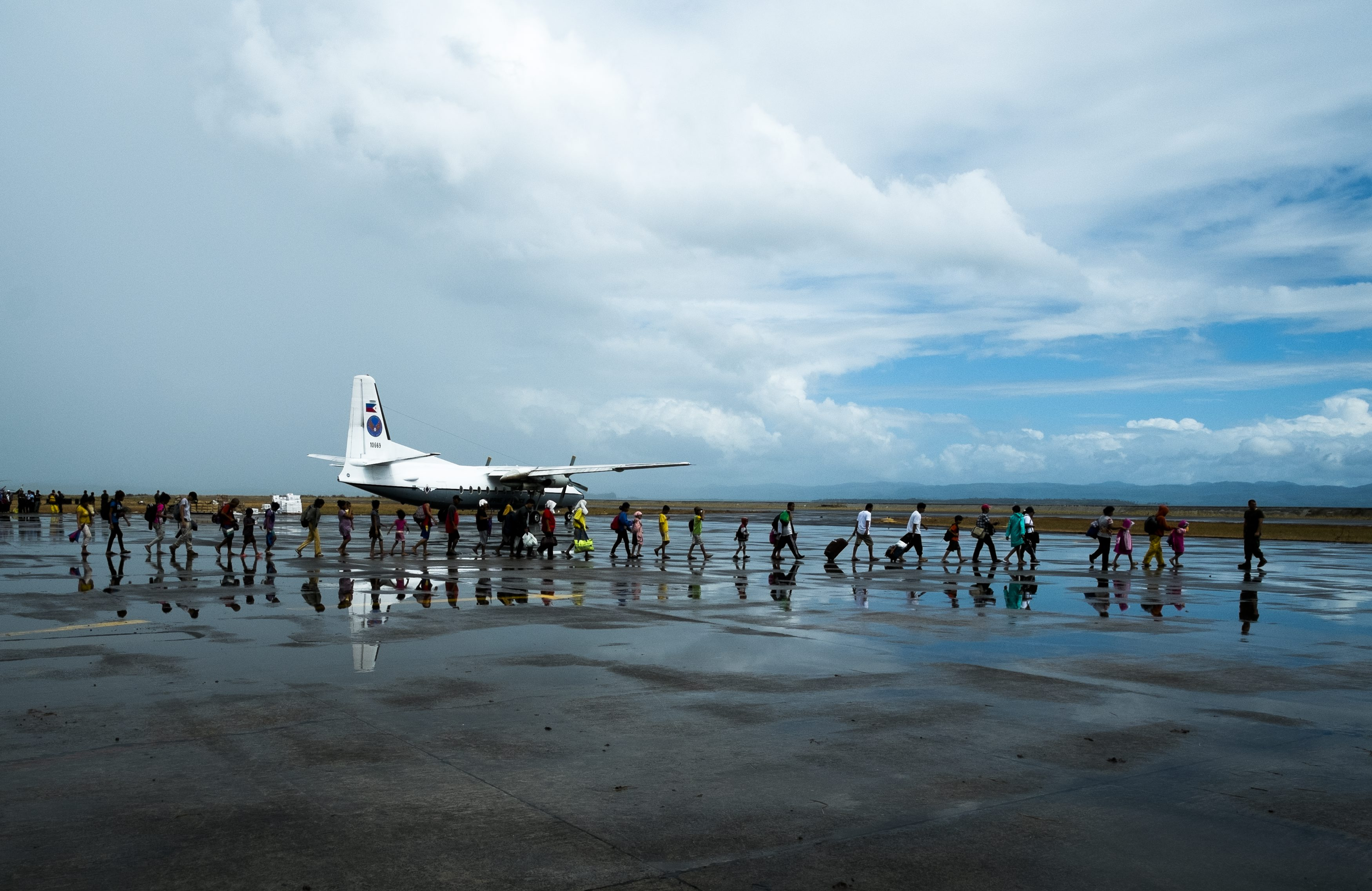 Philippines/ Haiyan Typhoon/Passengers line up to board C-130 plane for Cebu City at the tarmac of the damaged Tacloban Airport./ UNHCR/ R.Rocamora / November 2013